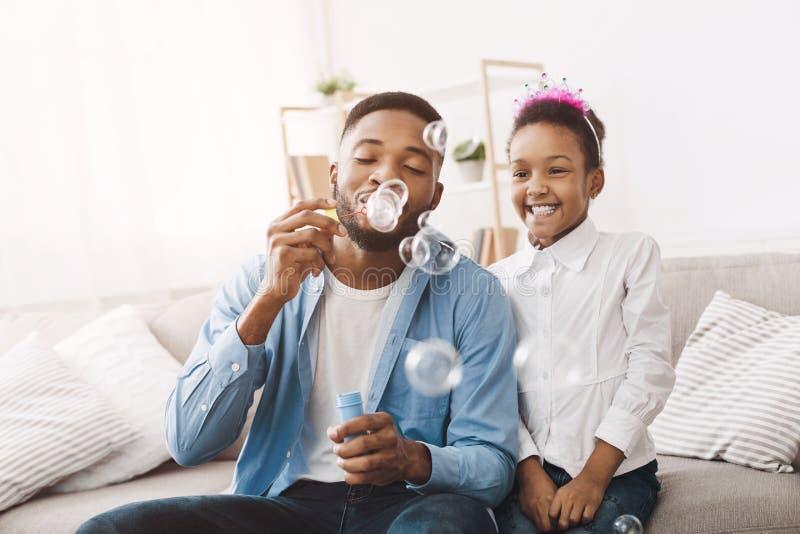 Bolhas de sabão de sopro do pai e da filha em casa imagem de stock