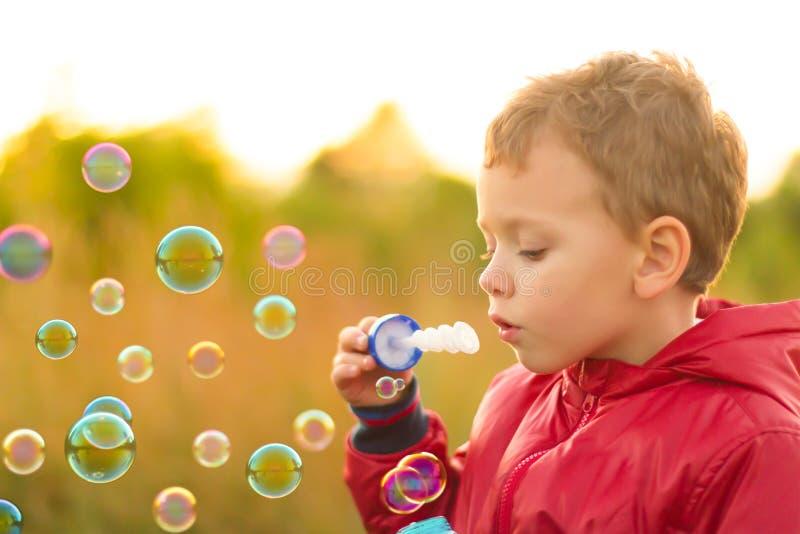 Bolhas de sabão de sopro do rapaz pequeno fora imagem de stock