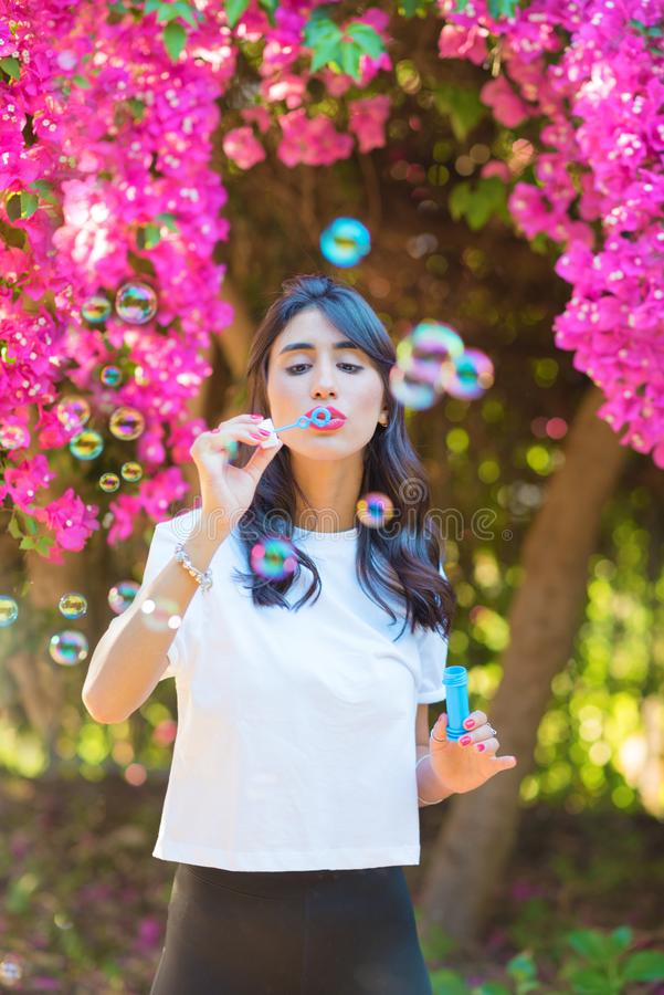 Bolhas de sab?o de sopro da jovem mulher bonita feliz exteriores fotos de stock royalty free