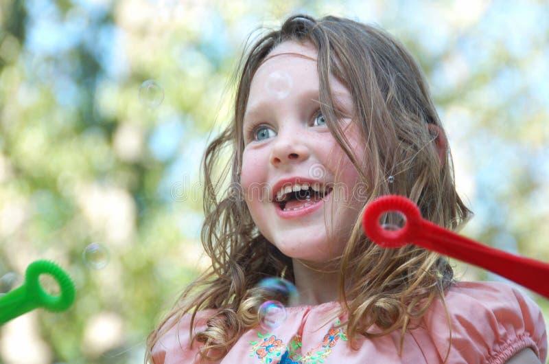 Bolhas de sopro da menina feliz fotos de stock royalty free