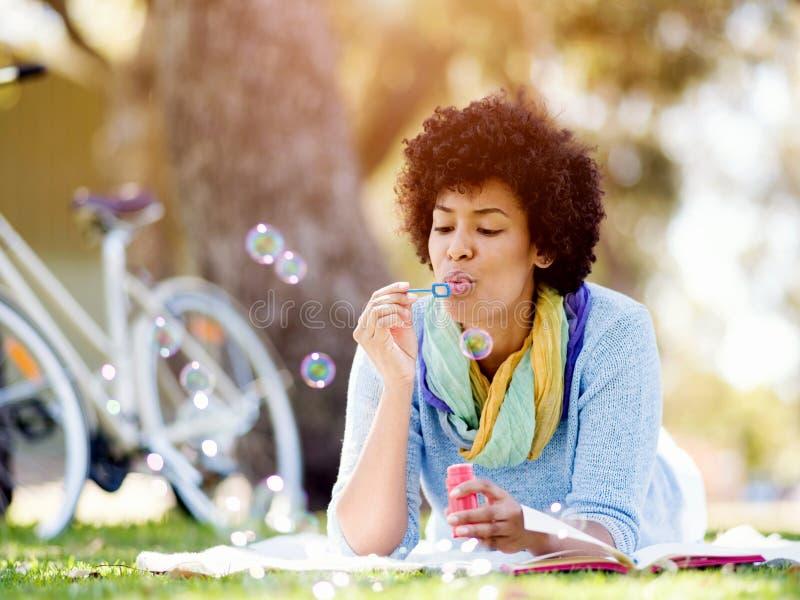 Bolhas de sopro da mulher bonita no parque fotografia de stock royalty free
