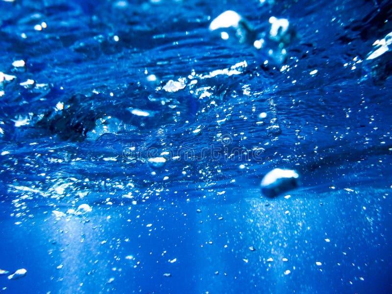 Bolhas de um mergulhador de mergulhador que aumenta à superfície no mar azul imagem de stock royalty free