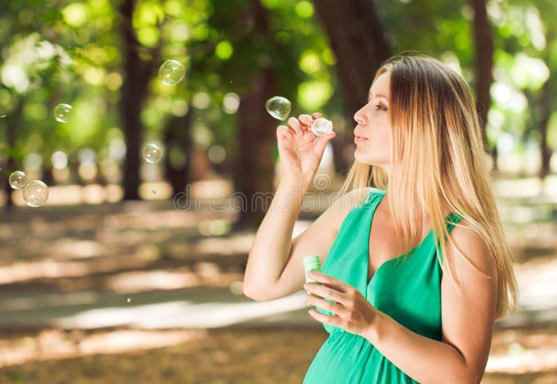 Bolhas louras felizes do sopro da mulher gravida no parque imagem de stock