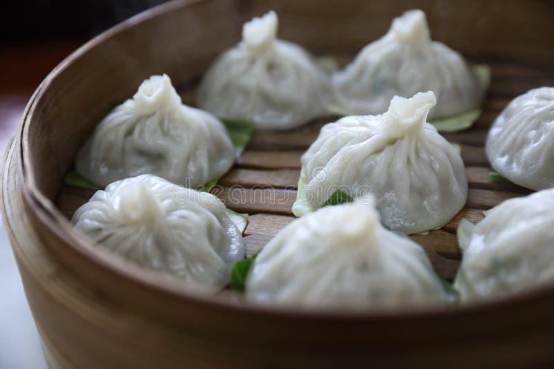 Bolinha de massa do dim sum na cesta de bambu, alimento chinês imagem de stock