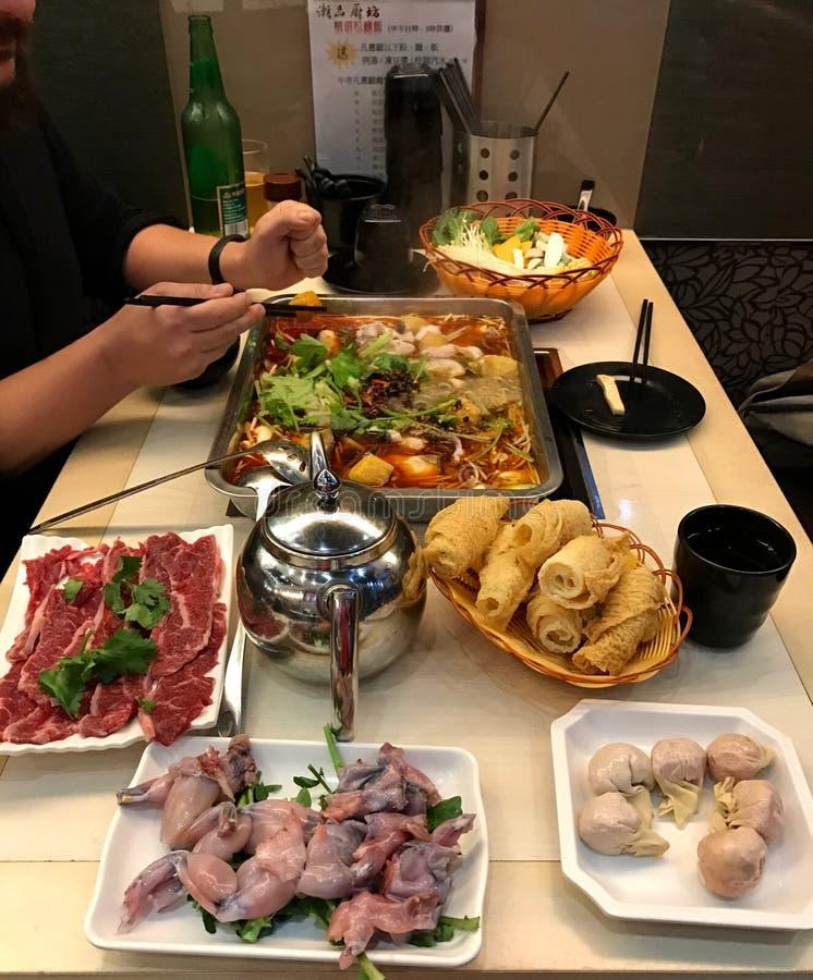 Bolinhas de massa chinesas, carne crua, pernas de sapo cruas na tabela, preparada auto-cozinhando em um fogão da indução no caldo fotografia de stock