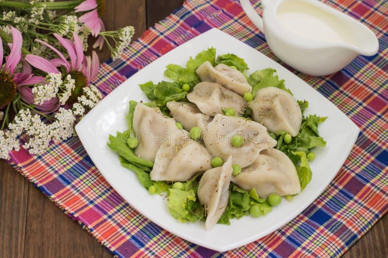 Bolinhas de massa com a galinha triturada em ervas frescas e em ervilhas de uma placa Fundo de madeira Close-up foto de stock royalty free