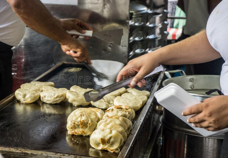Bolinhas de massa da carne que estão sendo servidas em um mercado livre imagens de stock