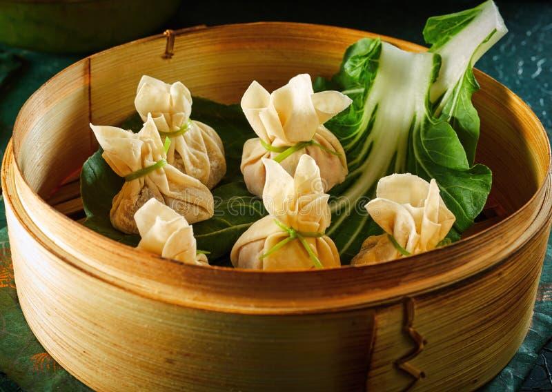 Bolinhas de massa do dim sum na cesta de bambu imagens de stock