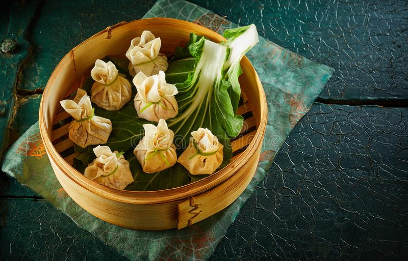 Bolinhas de massa do dim sum na folha verde na cesta de bambu fotos de stock royalty free
