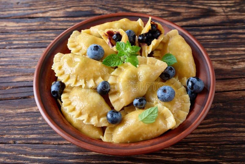 Bolinhas de massa do mirtilo, pierogi, vareniki em uma bacia fotografia de stock