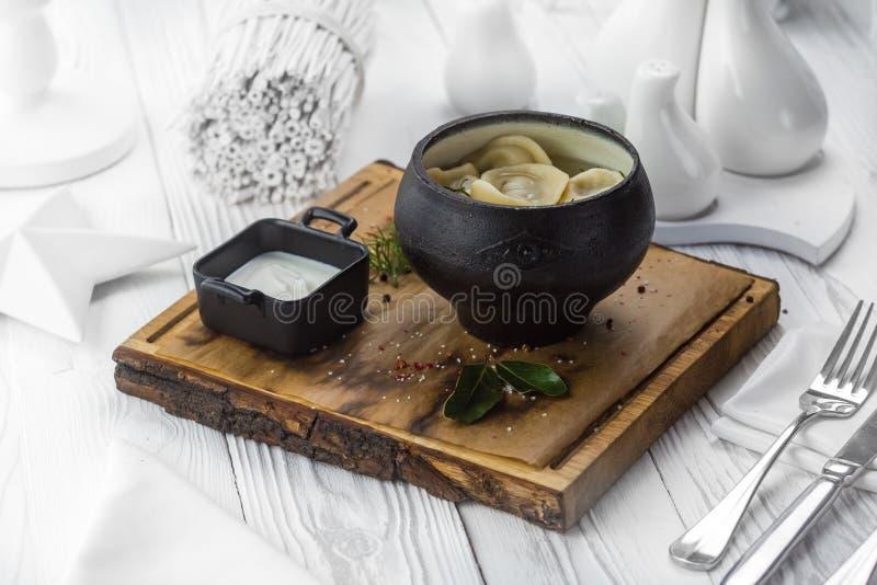 Bolinhas de massa do russo com creme de leite em um potenciômetro fotografia de stock royalty free