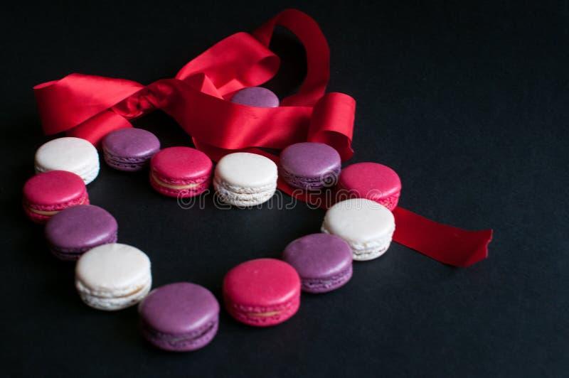 Bolinho de amêndoa apresentado em um fundo preto sob a forma de um coração com fita vermelha Cookies de amêndoa coloridas, cores  fotos de stock