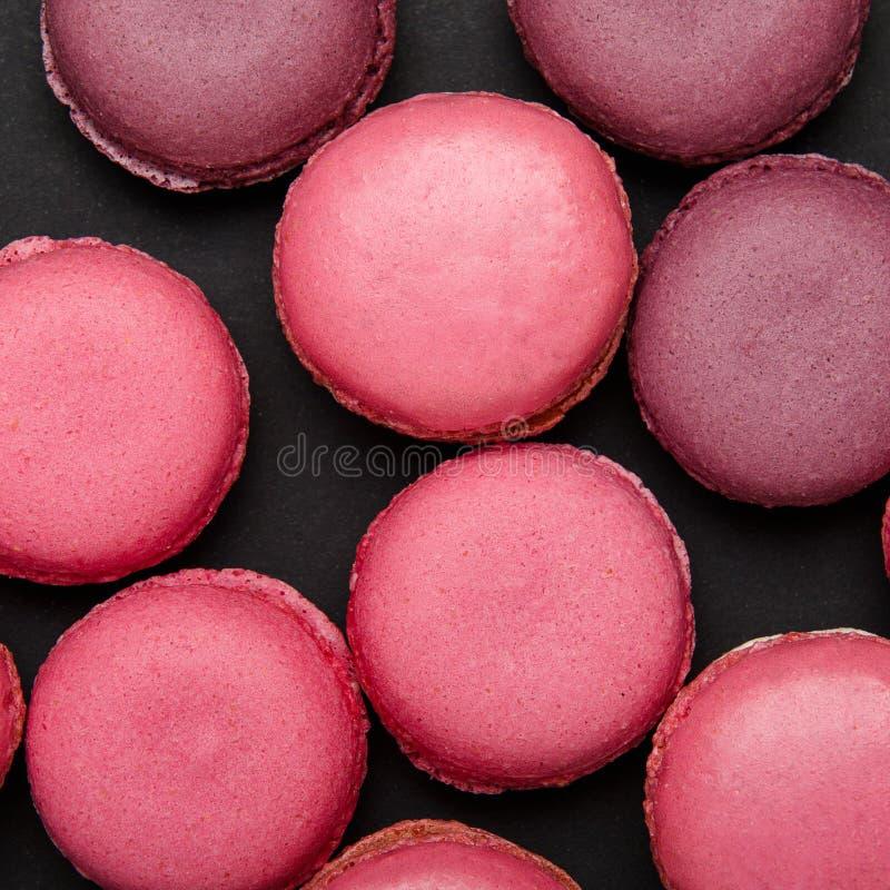 Bolinho de amêndoa cor-de-rosa colorido em um fundo preto, textura Deleite doce, biscoitos, alimento de alto-caloria Copie o espa fotografia de stock royalty free