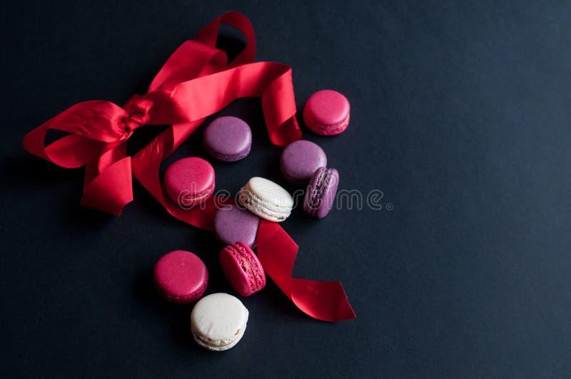 Bolinho de amêndoa no fundo preto com fita vermelha, cookies de amêndoa coloridas, cores pastel foto de stock royalty free