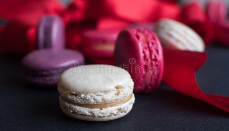 Bolinho de amêndoa no fundo preto com fita vermelha, cookies de amêndoa coloridas, cores pastel foto de stock