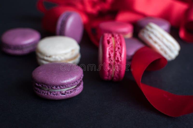 Bolinho de amêndoa no fundo preto com fita vermelha, cookies de amêndoa coloridas, cores pastel imagens de stock royalty free