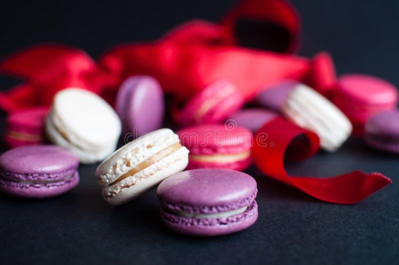 Bolinho de amêndoa no fundo preto com fita vermelha, cookies de amêndoa coloridas, cores pastel fotos de stock royalty free