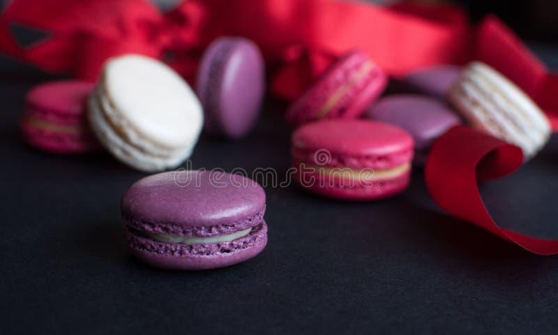 Bolinho de amêndoa no fundo preto com fita vermelha, cookies de amêndoa coloridas, cores pastel fotografia de stock royalty free