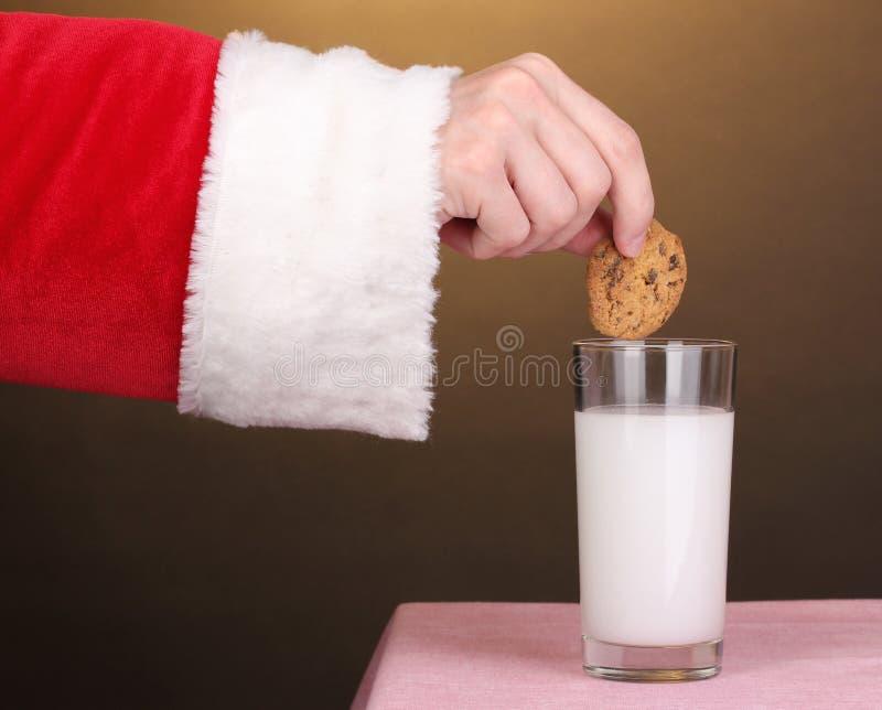 Bolinho do chocolate da terra arrendada da mão de Papai Noel fotografia de stock