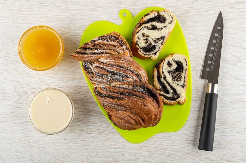 Bolinhos com leite condensado e mel, pãozinho com papoila no quadro de corte, faca na mesa de madeira Vista superior fotos de stock royalty free