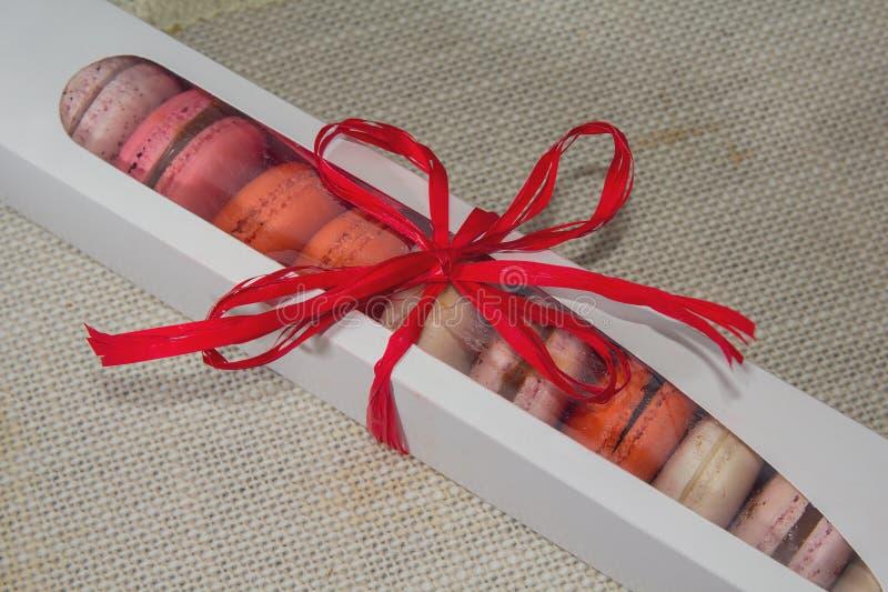 Bolinhos de amêndoa coloridos em uma caixa de presente no fundo de matéria têxtil fotografia de stock
