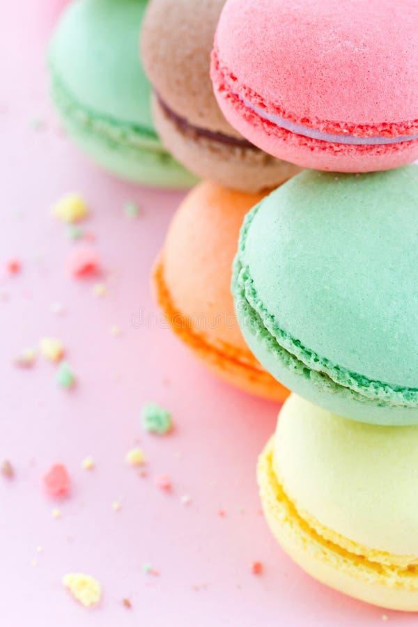 Bolinhos de amêndoa coloridos no fundo do rosa pastel imagem de stock royalty free