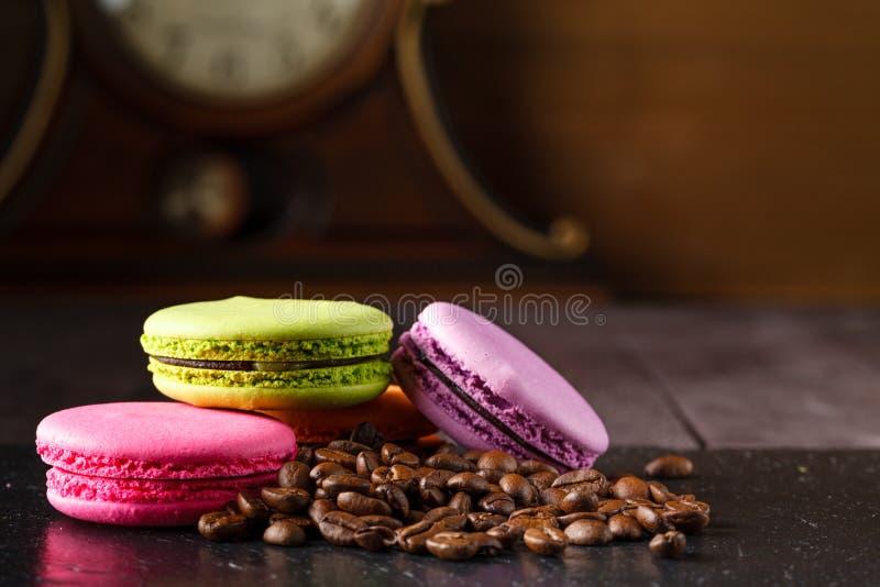Bolinhos de amêndoa de Colorfull com os feijões de café roasted imagem de stock royalty free