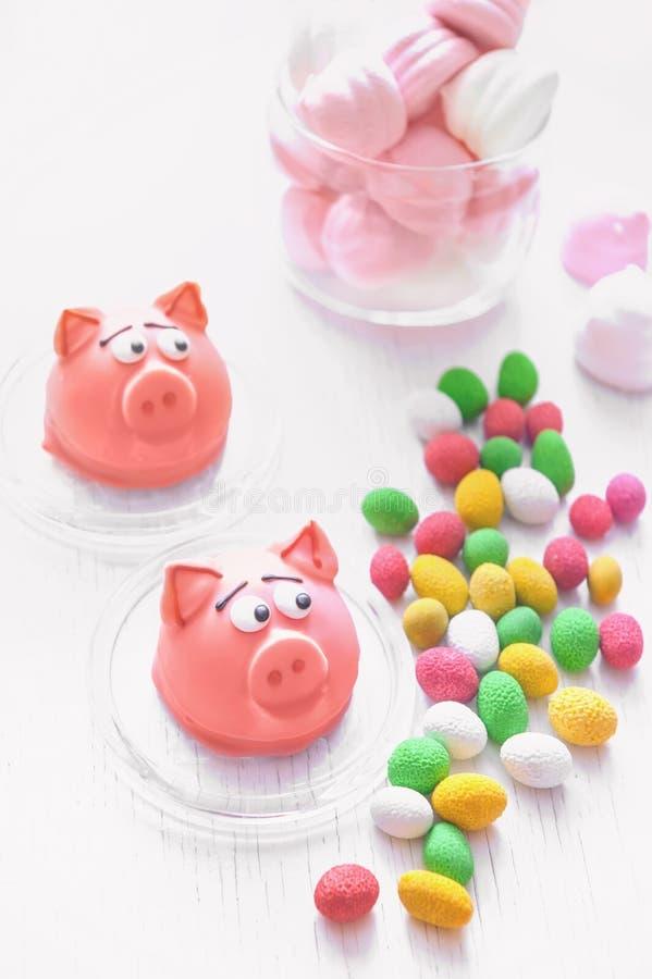 Bolinhos de amêndoa delicados doces do maçapão cor-de-rosa sob a forma dos marshmallows de um mini-porco, amendoins em cores past imagens de stock