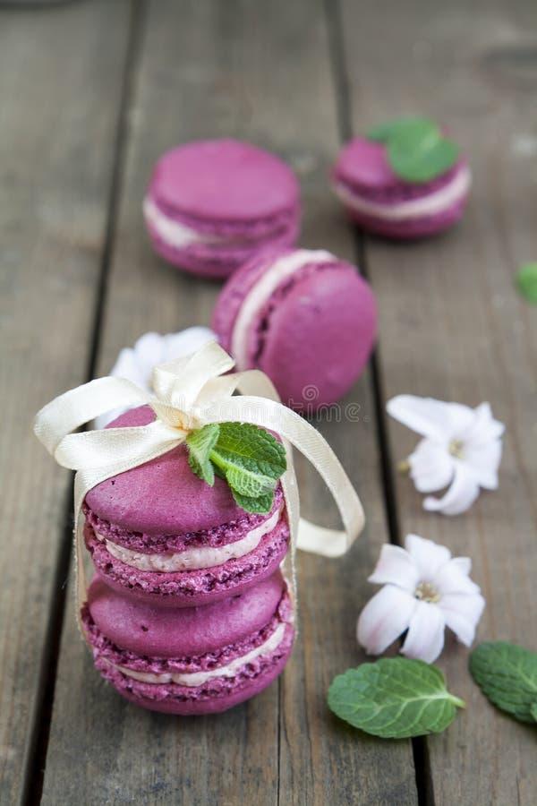 Bolinhos de amêndoa franceses carmesins doces com flores e hortelã do jacinto no fundo de madeira escuro imagens de stock royalty free