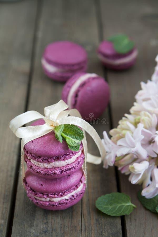Bolinhos de amêndoa franceses carmesins doces com flores e hortelã do jacinto no fundo de madeira escuro fotos de stock royalty free