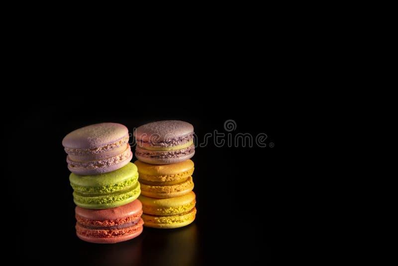 Bolinhos de amêndoa franceses do bolo, suporte colorido doce dos macarons em se em um fundo preto imagem de stock