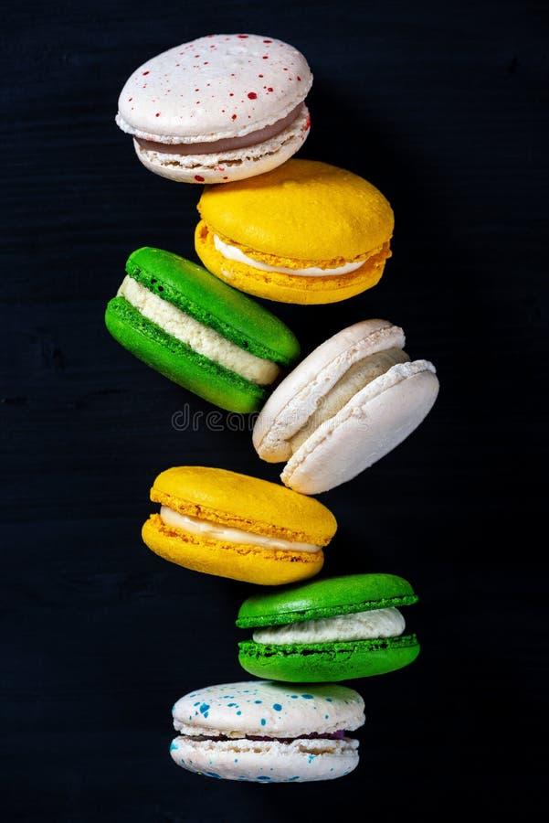 Bolinhos de amêndoa no fundo escuro, macarons franceses coloridos das cookies imagens de stock