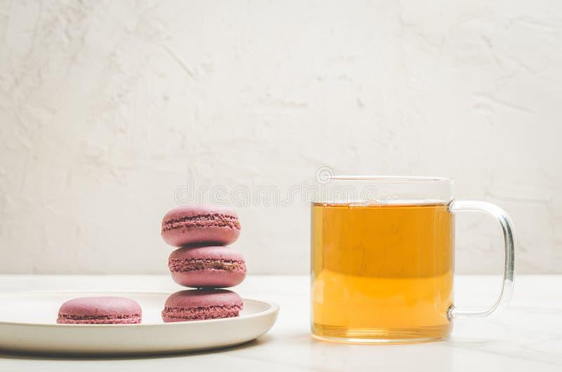 Bolinhos de amêndoa ou macaron e chá doces em um vidro em um fundo branco, sobremesa francesa imagens de stock royalty free