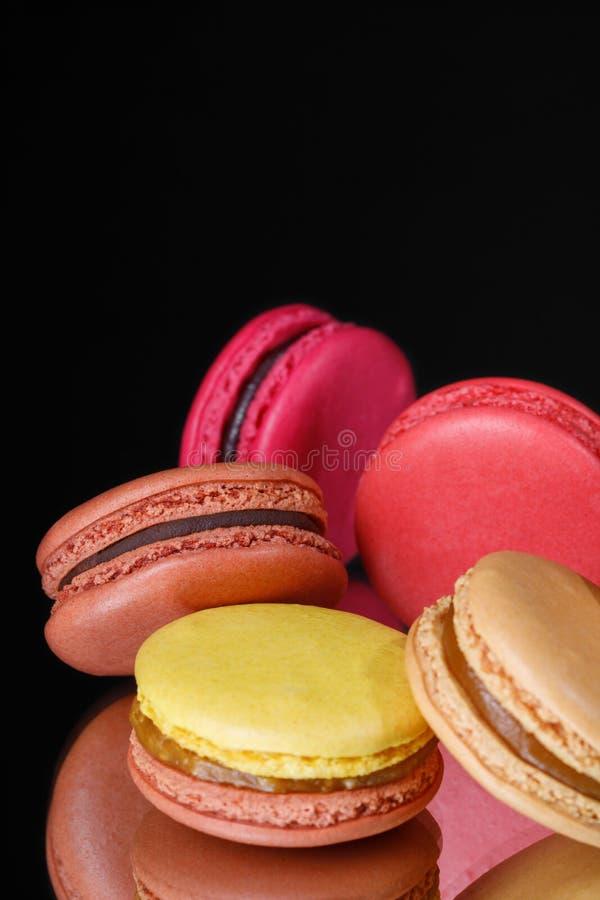 Bolinhos de amêndoa pasteis coloridos no fundo preto Macarons doces fotografia de stock royalty free