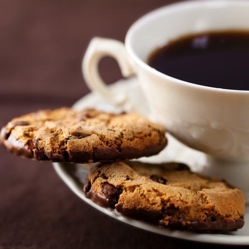 Bolinhos de microplaqueta de chocolate e uma chávena de café fotos de stock royalty free