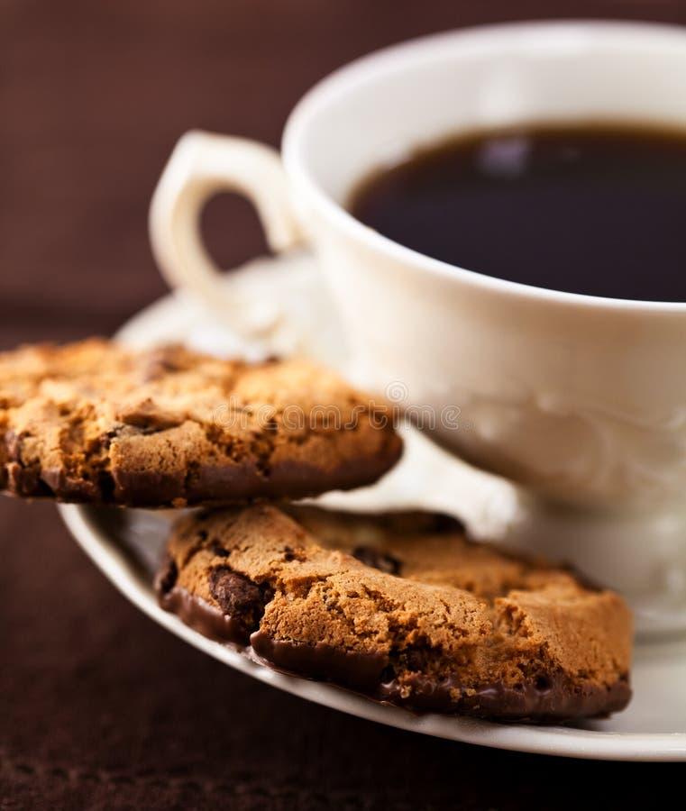 Bolinhos de microplaqueta de chocolate e uma chávena de café foto de stock royalty free