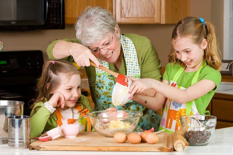 Bolinhos do cozimento da avó com crianças. fotografia de stock royalty free