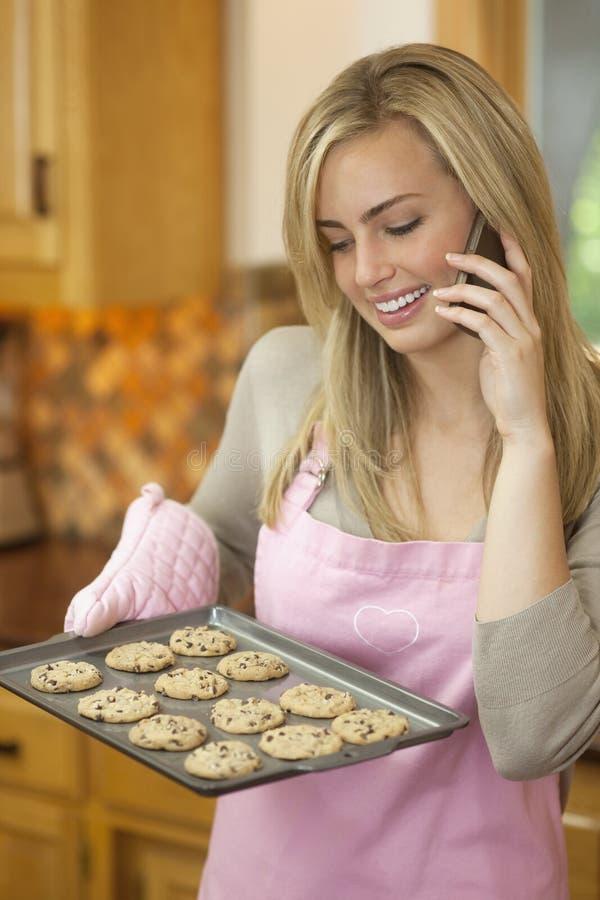 Bolinhos do cozimento da mulher e fala no telefone foto de stock