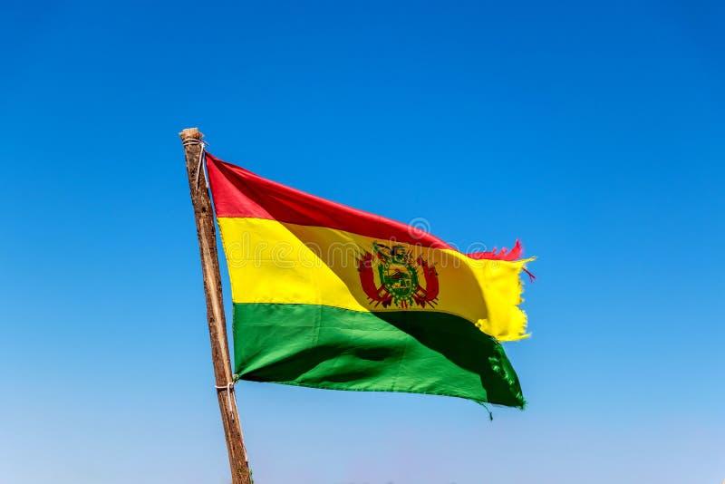 Bolivianer fahnenschwenkend im Wind gegen Hintergrund des blauen Himmels stockfotografie