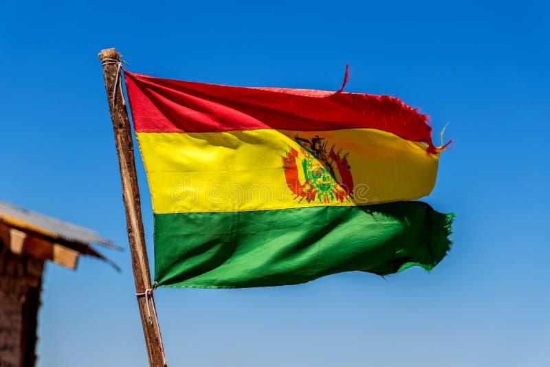 Bolivianer fahnenschwenkend im Wind gegen Hintergrund des blauen Himmels stockfotos