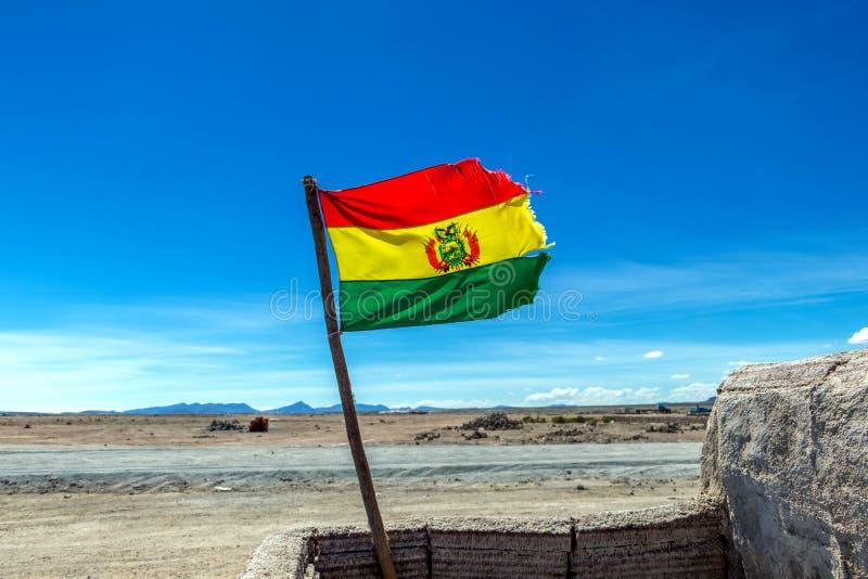 Bolivianer fahnenschwenkend im Wind gegen Hintergrund des blauen Himmels lizenzfreie stockbilder