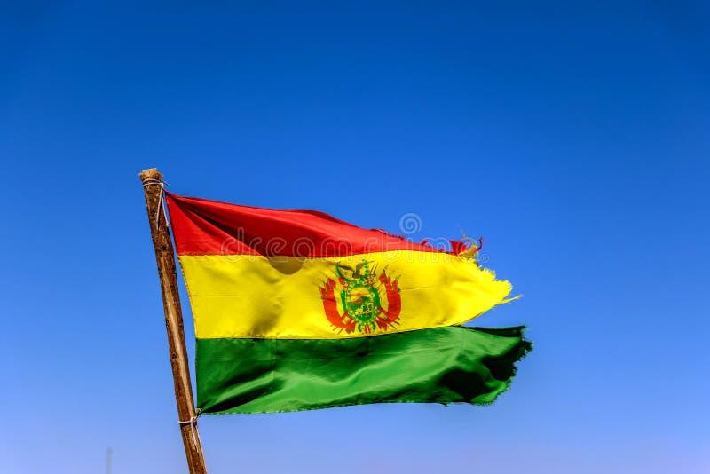 Bolivianer fahnenschwenkend im Wind gegen Hintergrund des blauen Himmels stockbild