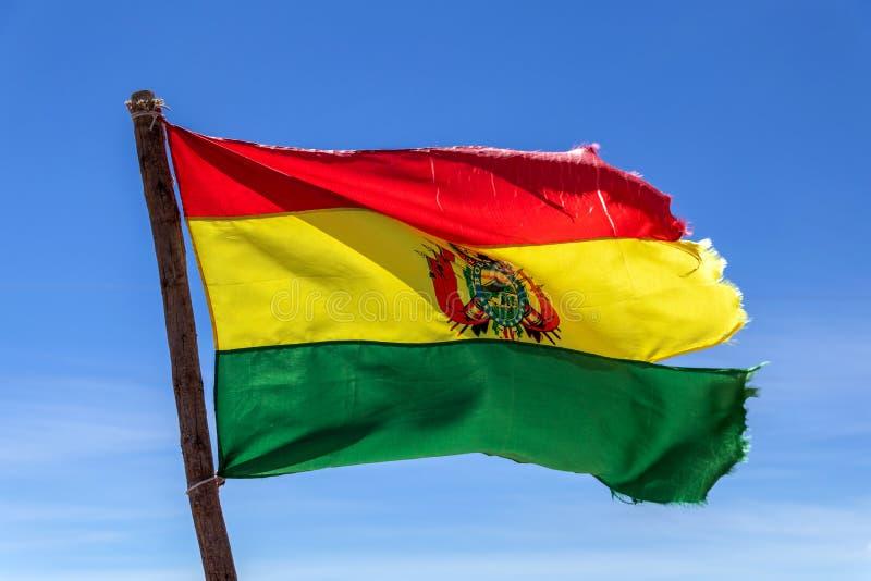 Bolivianer fahnenschwenkend im Wind gegen Hintergrund des blauen Himmels lizenzfreie stockfotografie