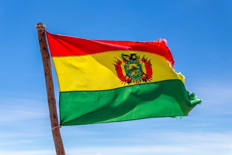 Bolivianer fahnenschwenkend im Wind gegen Hintergrund des blauen Himmels stockfoto