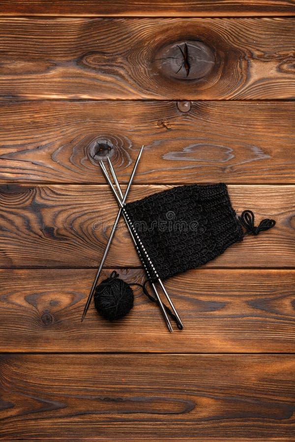 Boll av den svarta sticka tråden och stickmönstret på en träbakgrund arkivbild