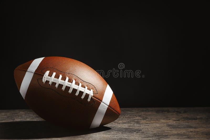 Boll för amerikansk fotboll på tabellen mot mörk bakgrund royaltyfria bilder