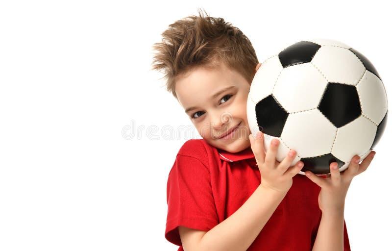 Boll för fotboll för håll för spelare för fansportpojke i den röda t-skjortan som firar lyckligt le skratta kopieringsutrymme för arkivbilder