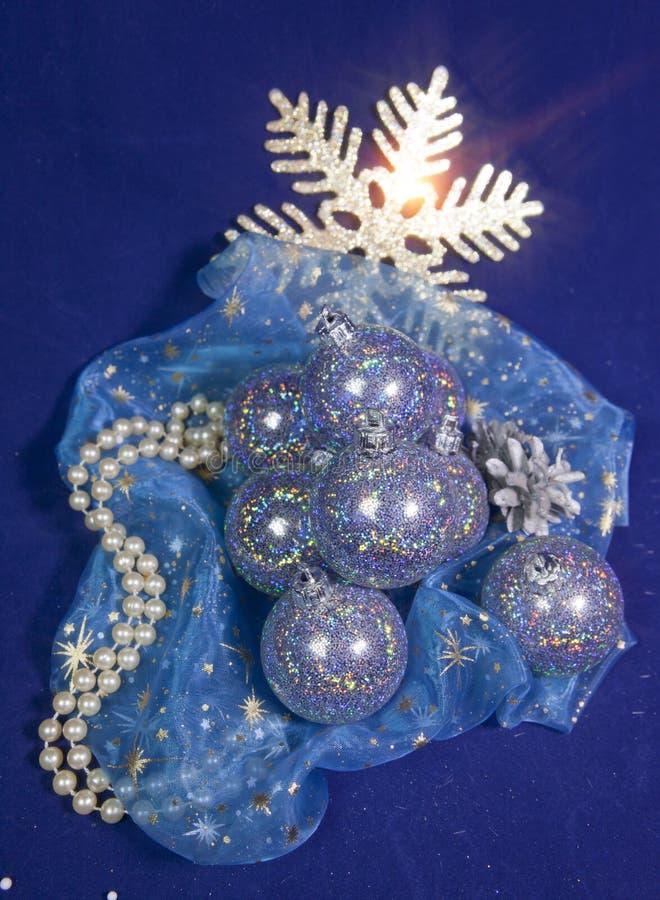 Bollar för nytt år som är den hällda violeten på festligt tyg med guld- snöflingor och pärlemorfärg smycken på en blå bakgrund royaltyfri foto