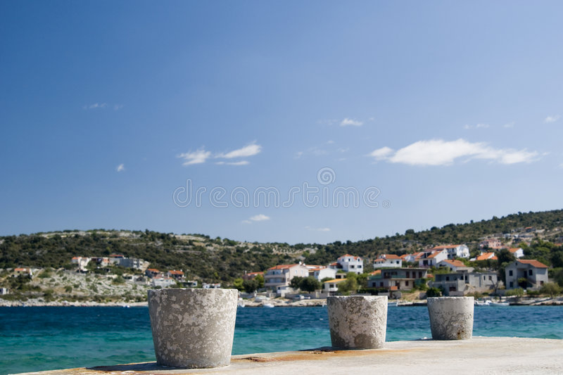 Bollard in the harbor. With city in the background during a sunny day with clouds - Croazia 2007 royalty free stock photography