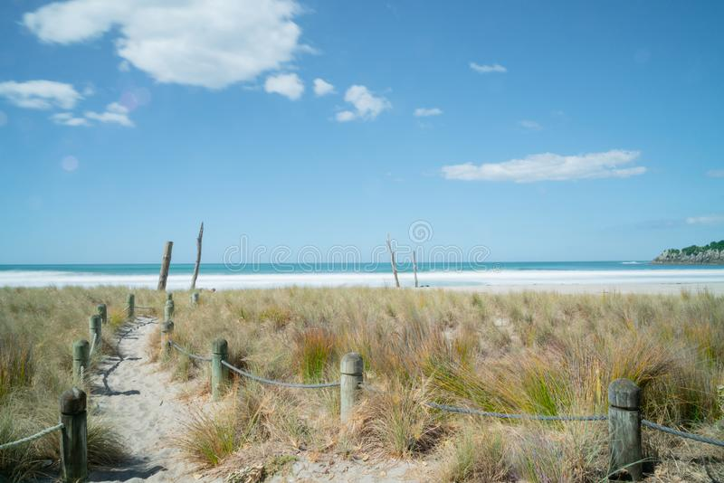 Bollards and rope line sad path to beach and water`s edge under blue sky with few white puffy clouds royalty free stock image